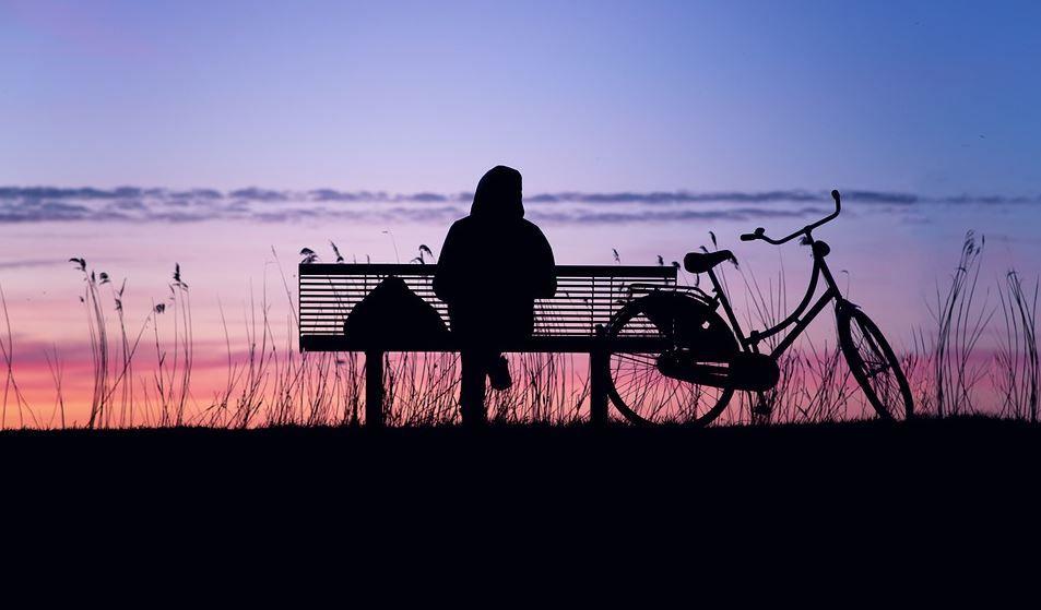 Vrouw op bankje bij zonsondergang